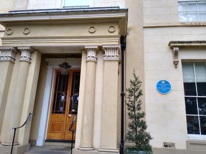 Blue plaque by the front door.